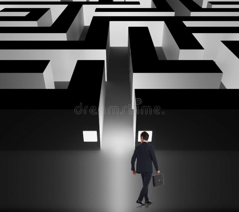 Homme d'affaires de marche décidant si entrer dans le labyrinthe d'affaires photo stock