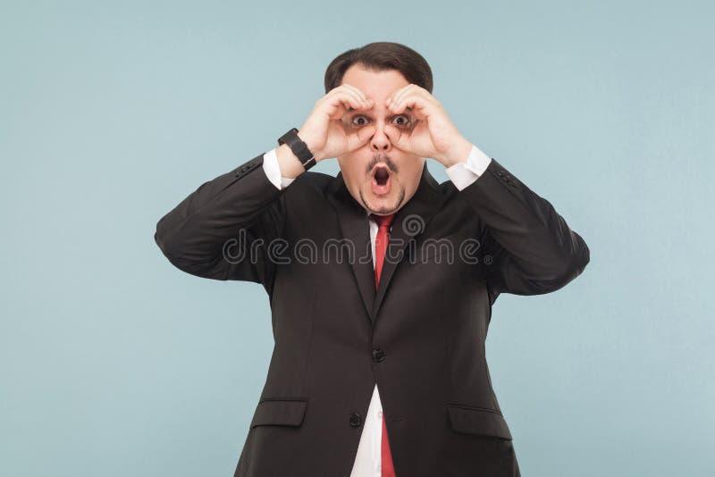 Homme d'affaires de merveille regardant loin Signe de jumelles image stock