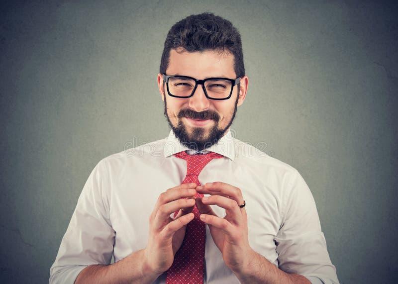 Homme d'affaires de Sly en verres regardant la caméra traçant une vengeance image libre de droits