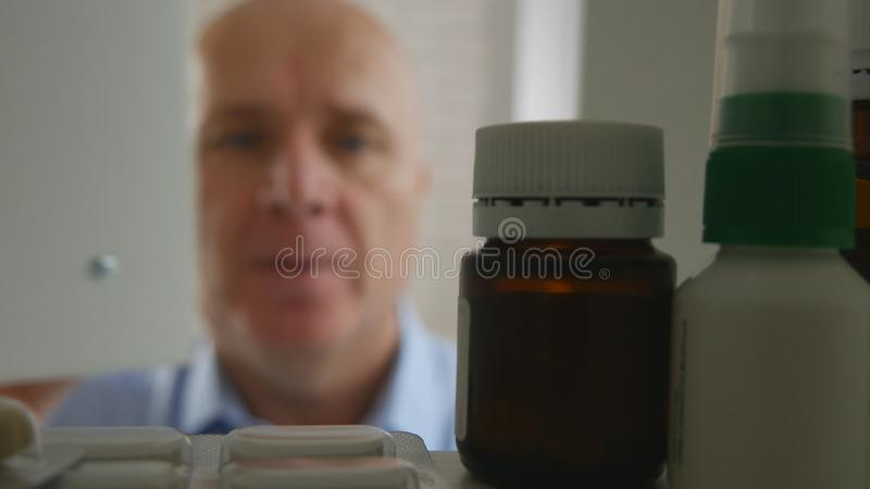 Homme d'affaires de souffrance recherchant les pilules médicales images stock