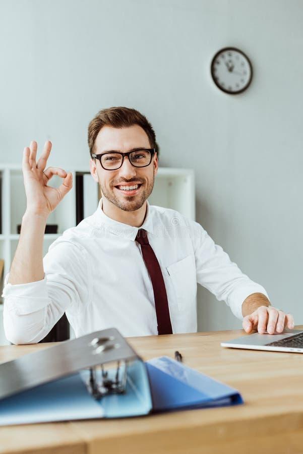 homme d'affaires de sourire élégant avec l'ordinateur portable et documents montrant le signe correct photographie stock