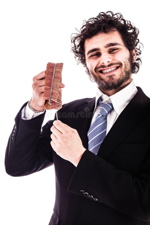 Homme d'affaires de sourire allumant les pétards rouges photo stock