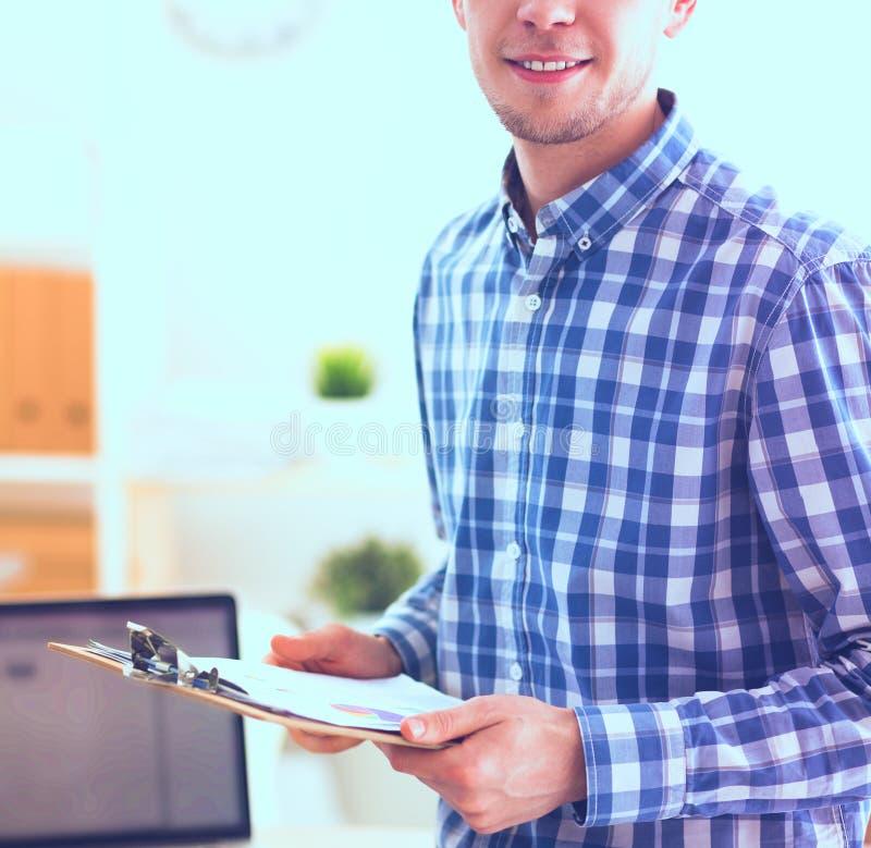 Homme d'affaires de sourire avec le dossier rouge se reposant dans le bureau images stock