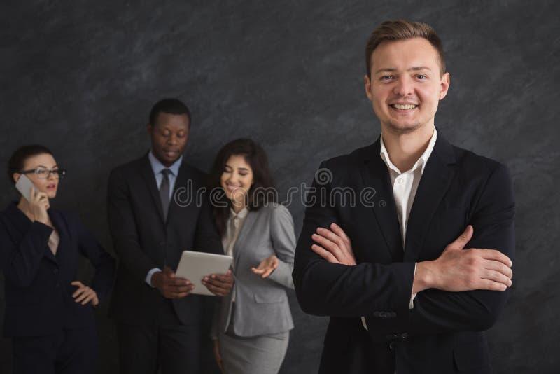 Homme d'affaires de sourire avec son équipe au fond image libre de droits