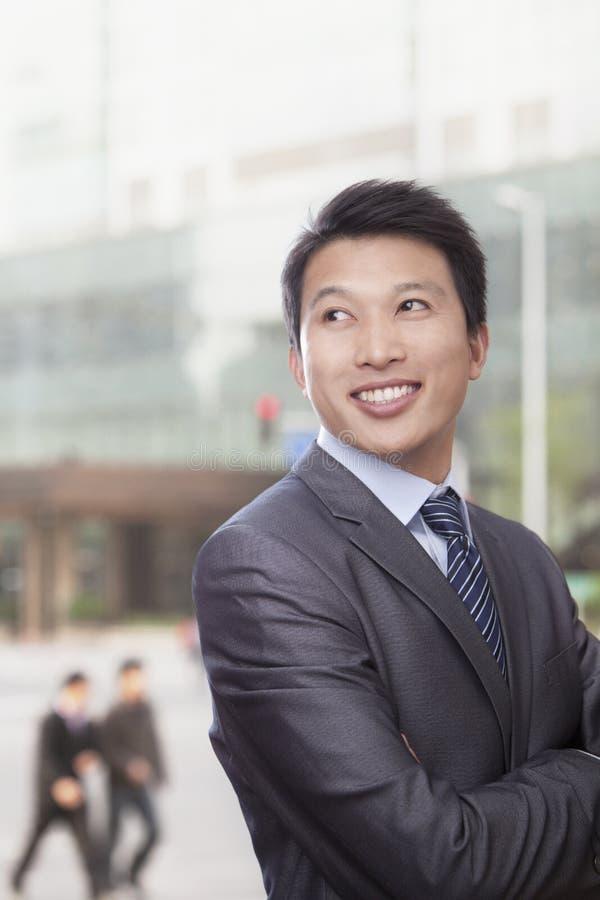 Homme d'affaires de sourire devant le bâtiment regardant loin photos stock