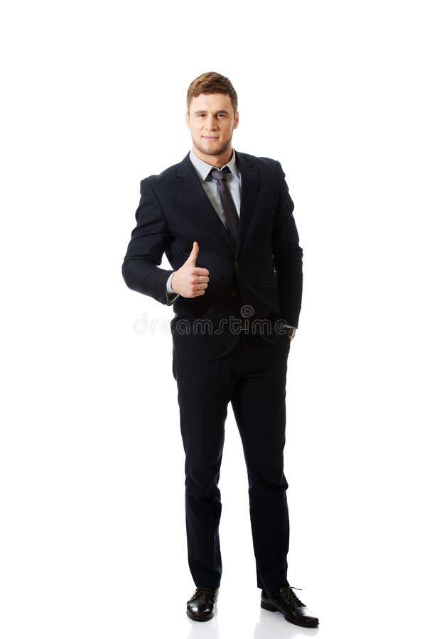 Homme d'affaires de sourire heureux avec des pouces  photographie stock