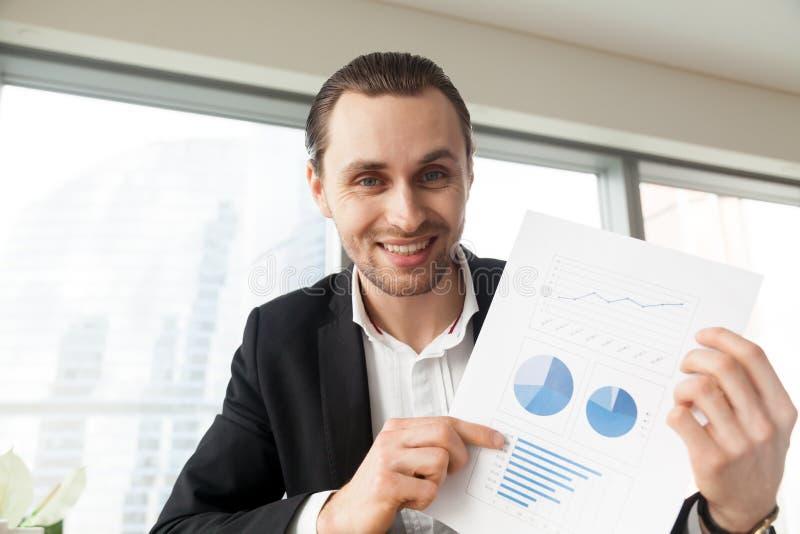 Homme d'affaires de sourire heureux dans le bureau montrant r financier positif photos stock