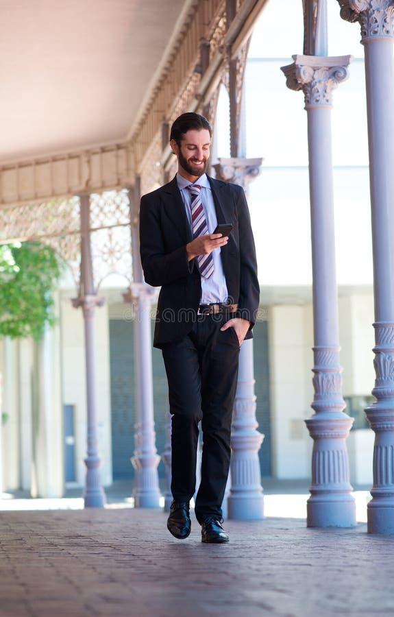 Homme d'affaires de sourire marchant sur le trottoir avec le téléphone portable images libres de droits