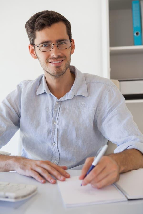 Homme d'affaires de sourire occasionnel prenant des notes à son bureau image libre de droits