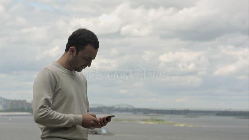 Homme d'affaires de sourire parlant au téléphone portable près de la rivière photo stock