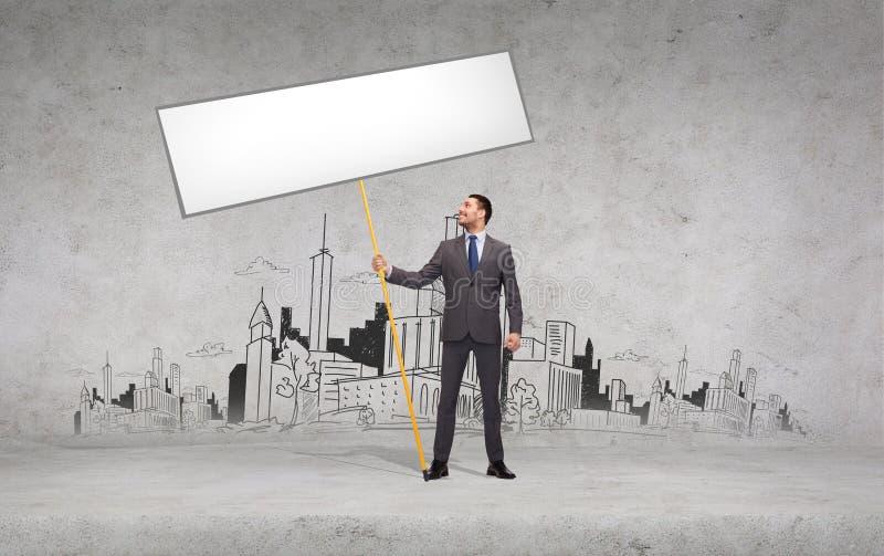 Homme d'affaires de sourire retenant le panneau blanc blanc images libres de droits