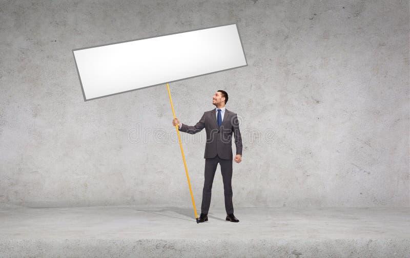 Homme d'affaires de sourire retenant le panneau blanc blanc photographie stock