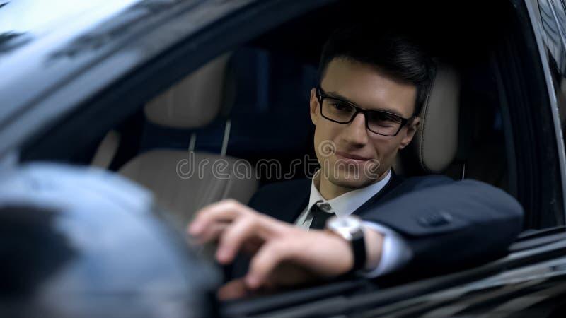 Homme d'affaires de sourire s'asseyant dans la voiture, regardant le miroir de vue arrière, voiture d'essai photographie stock libre de droits