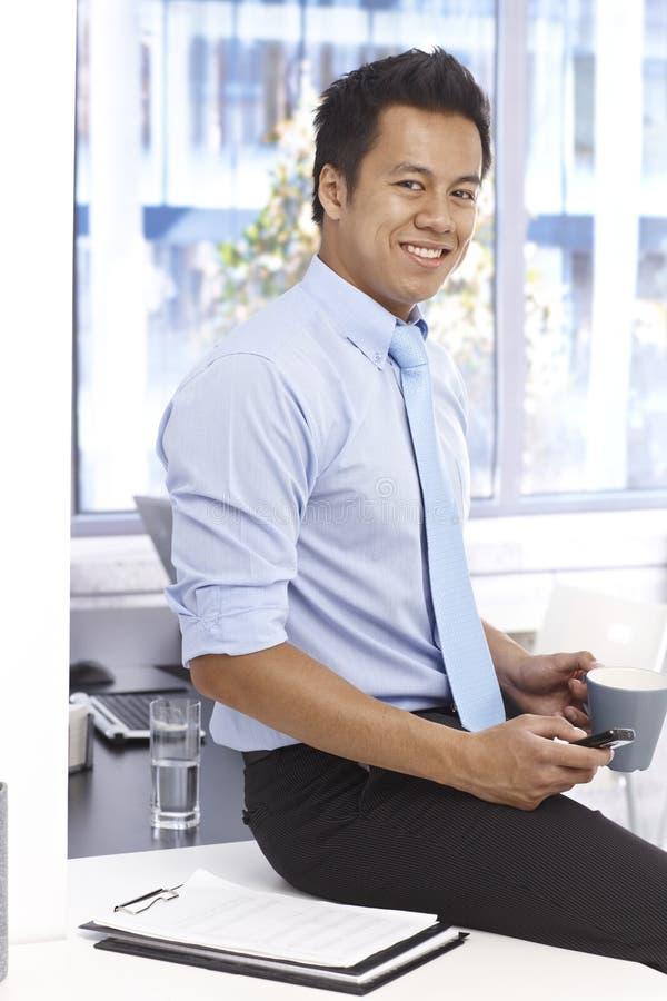 Homme d'affaires de sourire s'asseyant sur le bureau dans le bureau photographie stock