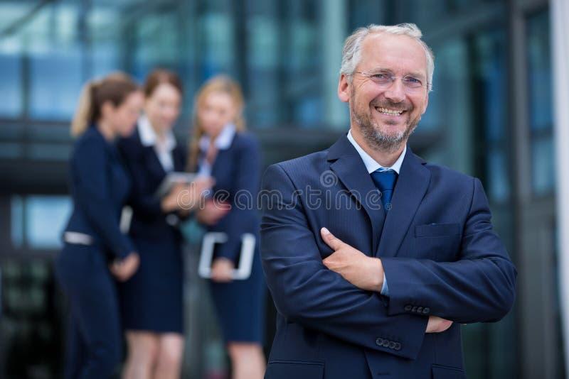 Homme d'affaires de sourire se tenant avec des bras croisés photos stock