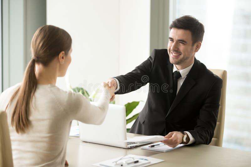 Homme d'affaires de sourire serrant la main à la femme d'affaires, tenant l'AG photo stock
