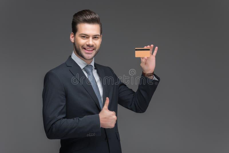 homme d'affaires de sourire tenant la carte de crédit d'or et montrant le pouce, photographie stock