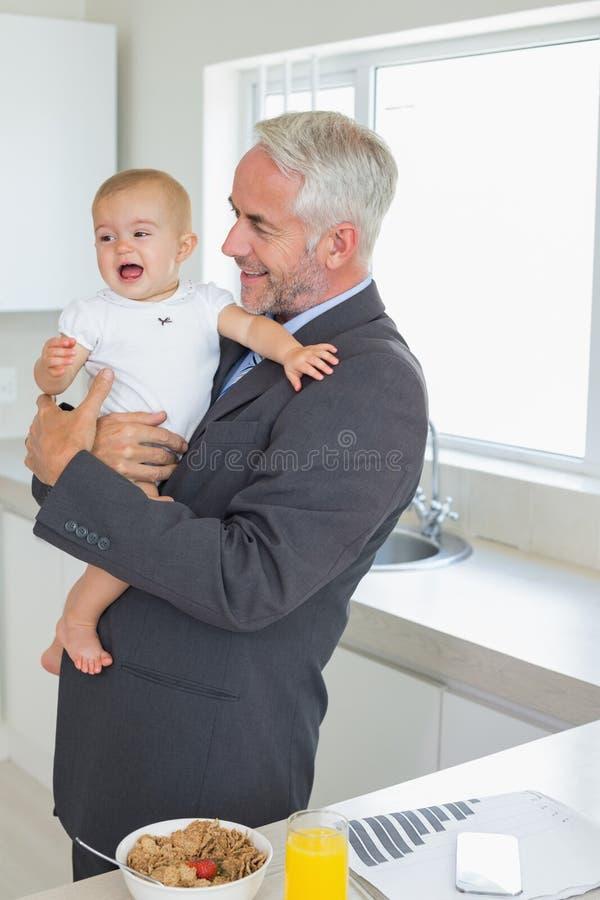 Homme d'affaires de sourire tenant son bébé pendant le matin avant travail image libre de droits