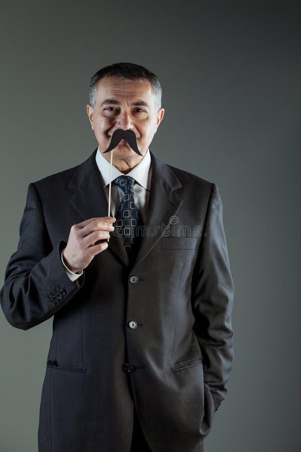 Homme d'affaires de sourire tenant une moustache photo stock