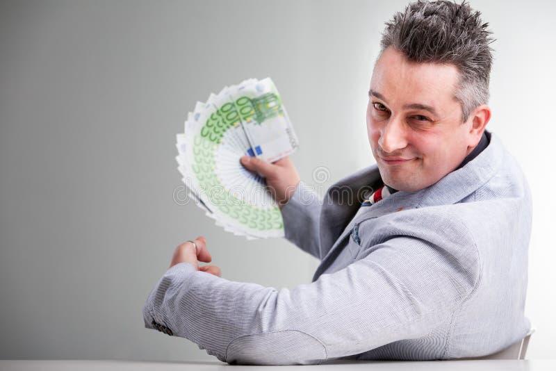 Homme d'affaires de sourire tenant une poignée de billets de banque photos stock