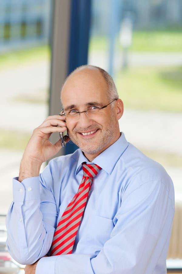 Homme d'affaires de sourire Using Cell Phone dans le bureau photographie stock libre de droits