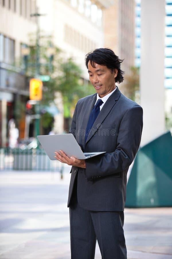 Homme d'affaires de sourire utilisant l'ordinateur portatif photo libre de droits