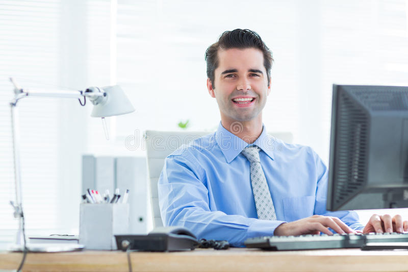 Download Homme D'affaires De Sourire Utilisant Son Ordinateur Photo stock - Image du workplace, lampe: 56482680