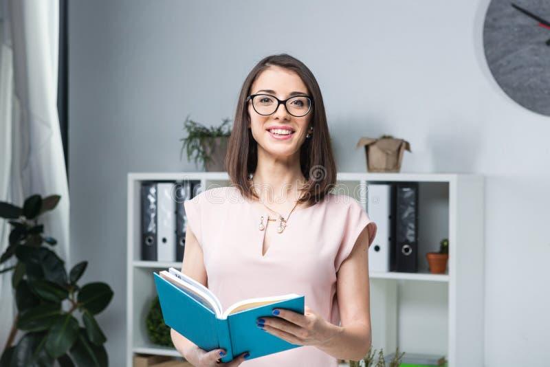 Homme d'affaires de thème La belle jeune femme caucasienne dans les verres et la chemise se tient près du bureau, tenant un carne images libres de droits