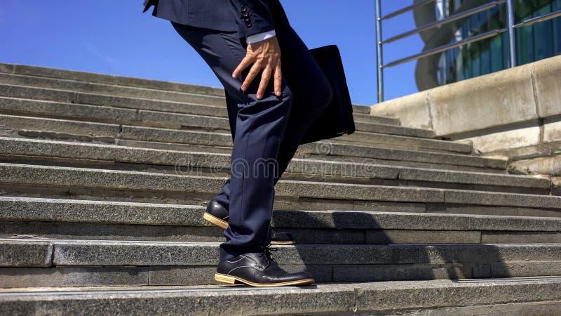 Homme d'affaires descendant des escaliers sentant la douleur forte de genou, inflammation commune images stock