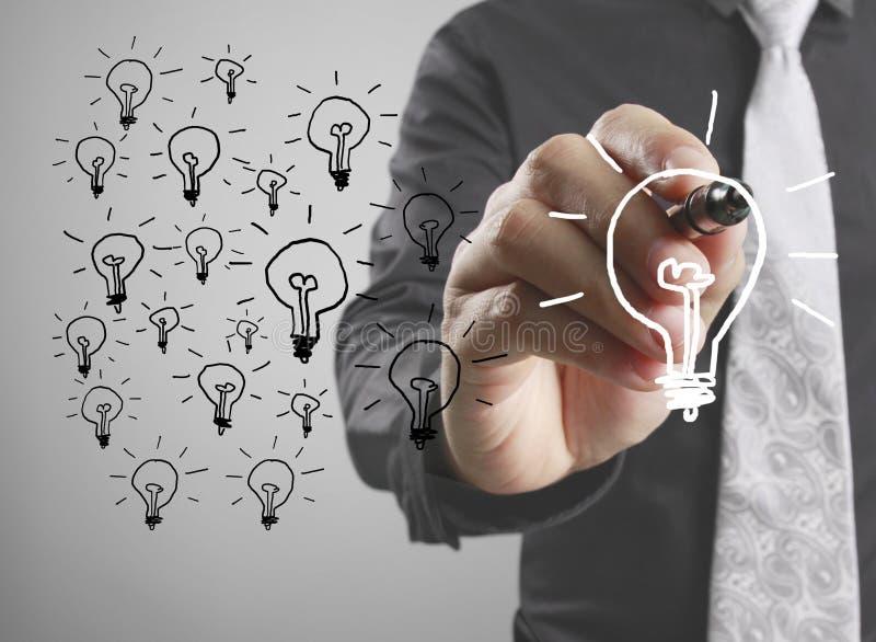 Homme d'affaires dessinant l'ampoule image libre de droits