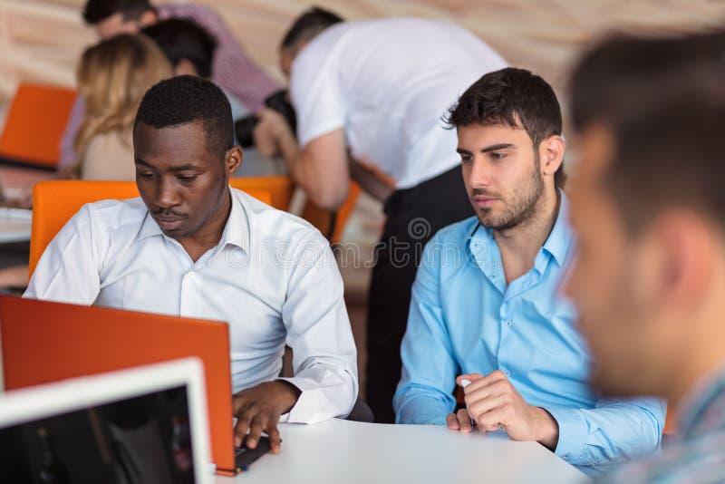 Homme d'affaires deux futé utilisant le workig de smartphone et d'ordinateur portable dans le bureau photographie stock libre de droits