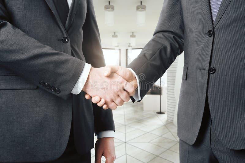 Homme d'affaires deux se serrant la main dans un bureau moderne léger image libre de droits