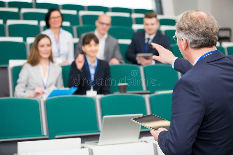 Homme d'affaires With Digital Tablet expliquant dans le séminaire Hall photo stock