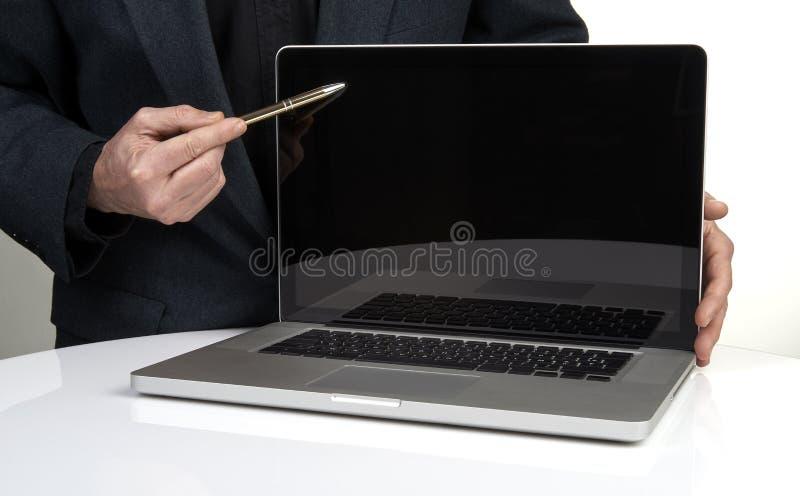 Homme d'affaires dirigeant l'ordinateur portable avec un stylo photographie stock libre de droits