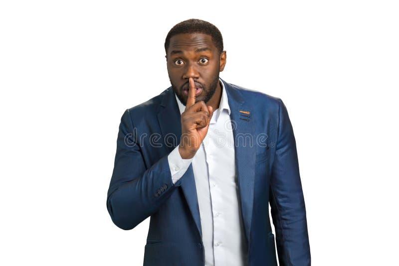 Homme d'affaires dirigeant le doigt au-dessus des lèvres image stock