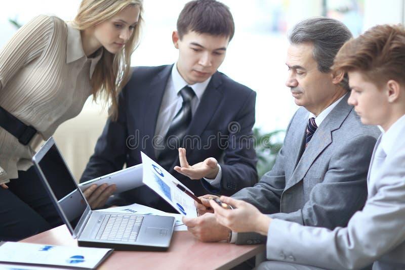 Homme d'affaires discutant avec les documents de travail d'équipe d'affaires images stock