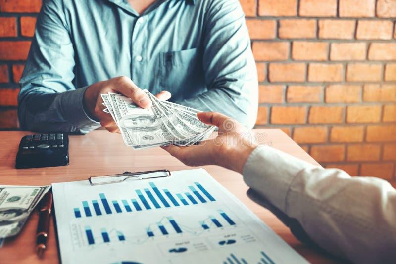 Homme d'affaires donnant l'argent à l'associé tout en faisant contre images libres de droits