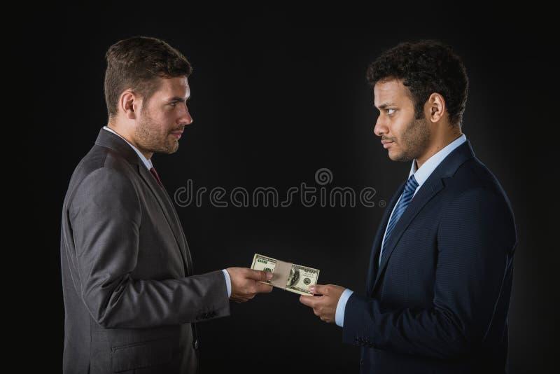 Homme d'affaires donnant l'argent et subornant l'associé photographie stock libre de droits