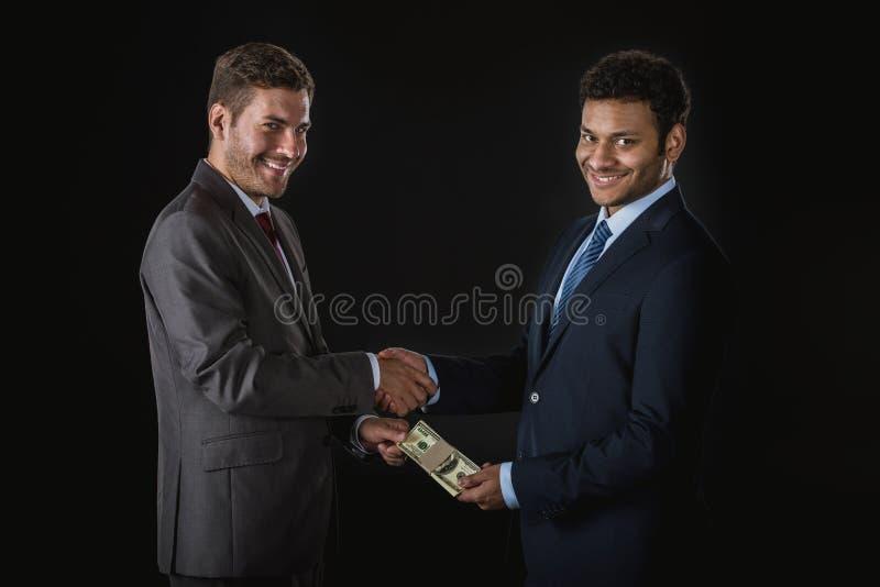 Homme d'affaires donnant l'argent et subornant l'associé d'isolement sur le noir photographie stock