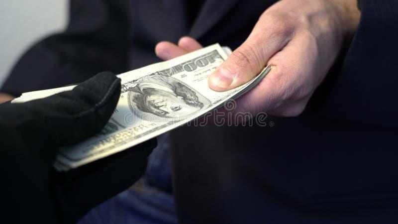 Homme d'affaires donnant l'argent pour donner les gants noirs, paiement illicite de concept de crime photo libre de droits