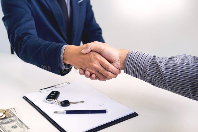 Homme d'affaires donnant la clé de fin au client après bon accord d'affaire tandis que convention de prêt étant approuvée et calc photo libre de droits
