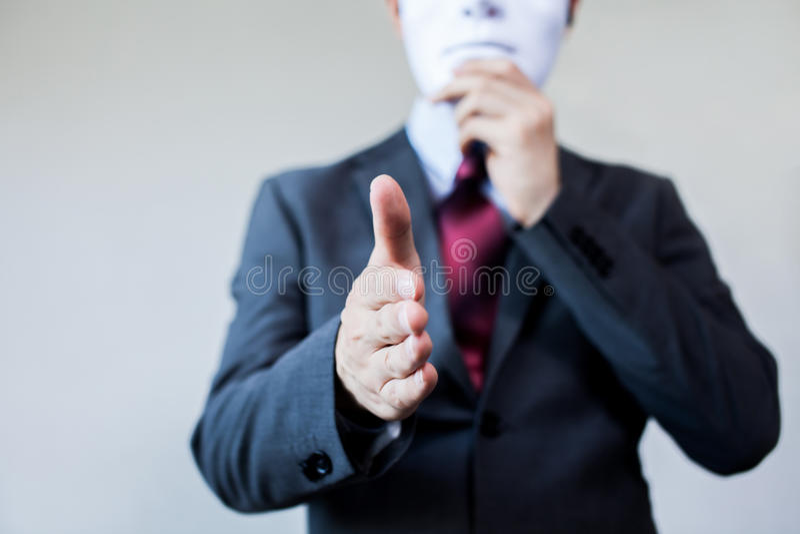 Homme d'affaires donnant la poignée de main malhonnête se cachant dans le masque - fraude d'affaires et accord d'hypocrite photo libre de droits