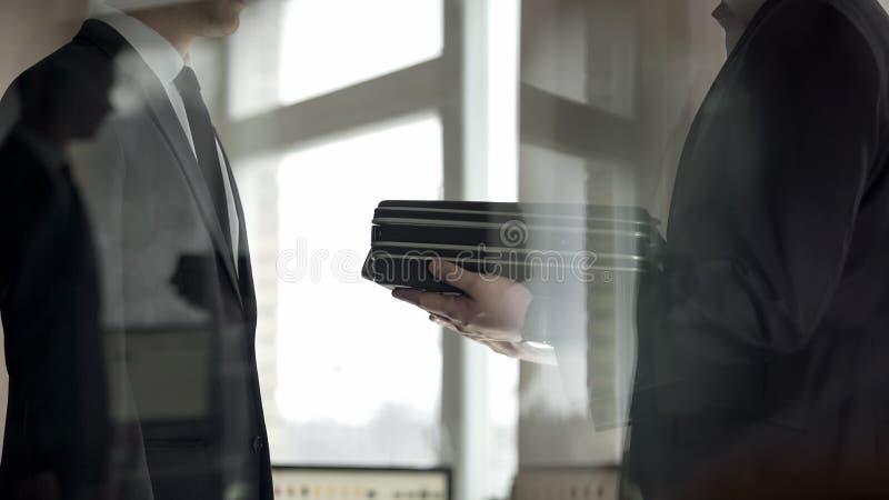 Homme d'affaires donnant la serviette d'argent ? l'associ?, affaire ill?gale, corruption photos stock