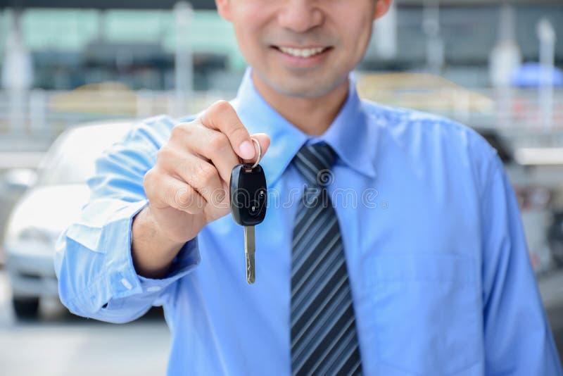 Homme d'affaires donnant une clé de voiture photo stock