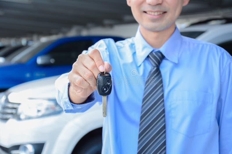 Homme d'affaires donnant une clé de voiture photos stock