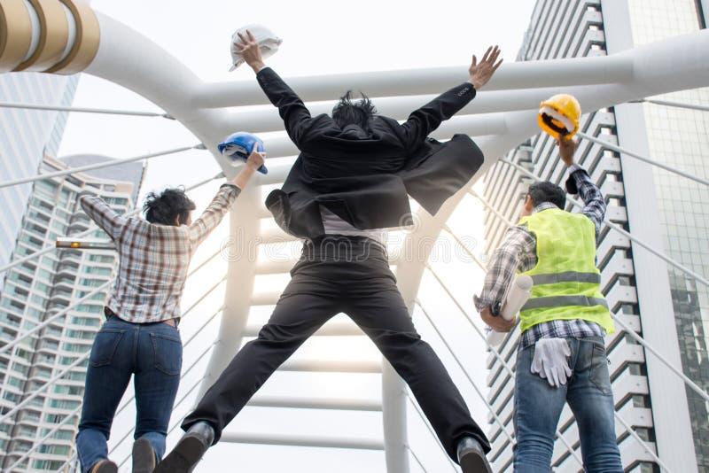 Homme d'affaires drôle et ingénieurs gais sautant en air et soulevant des bras avec le travail au succès, fond de ville images stock