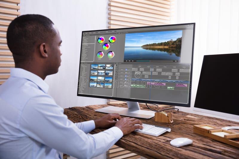 Homme d'affaires Editing The Video sur l'ordinateur photographie stock