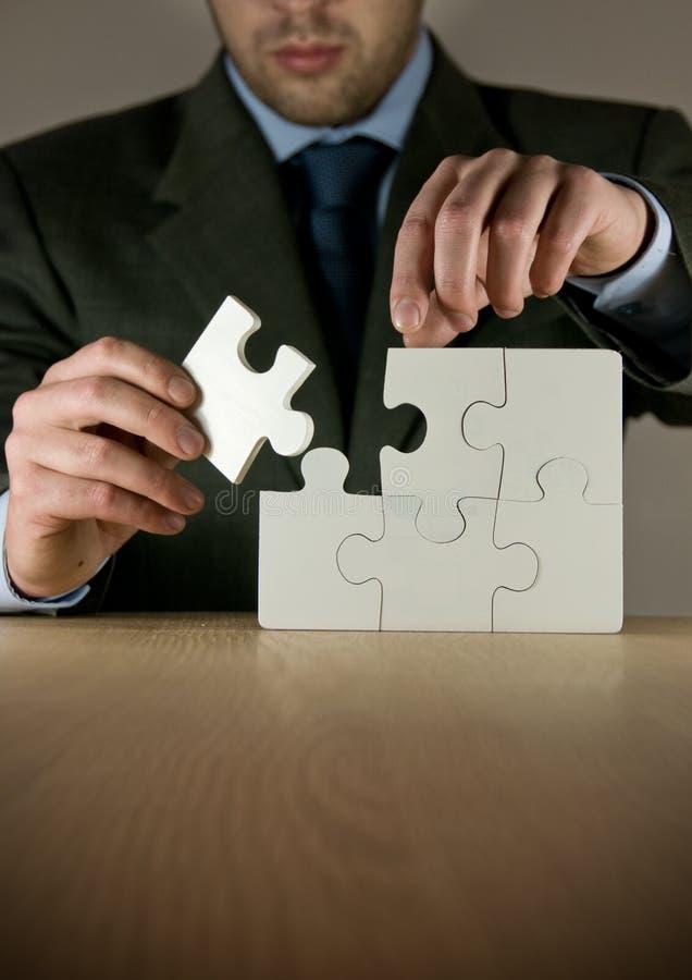 Homme d'affaires effectuant un puzzle photographie stock libre de droits