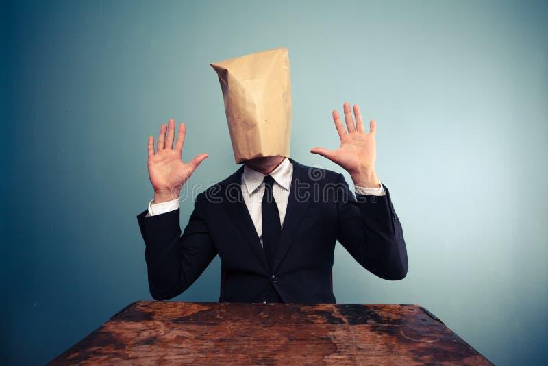 Homme d'affaires effrayé avec des frais généraux de sac soulevant ses mains image libre de droits