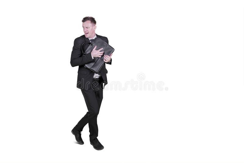 Homme d'affaires effrayé courant loin dans le studio photos stock